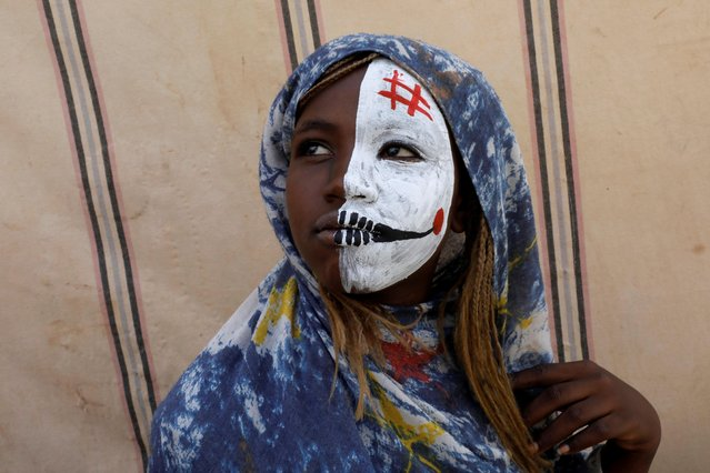 A Sudanese girl with half painted face watches as protesters demonstrate outside the defense ministry compound in Khartoum, Sudan, April 25, 2019. (Photo by Umit Bektas/Reuters)