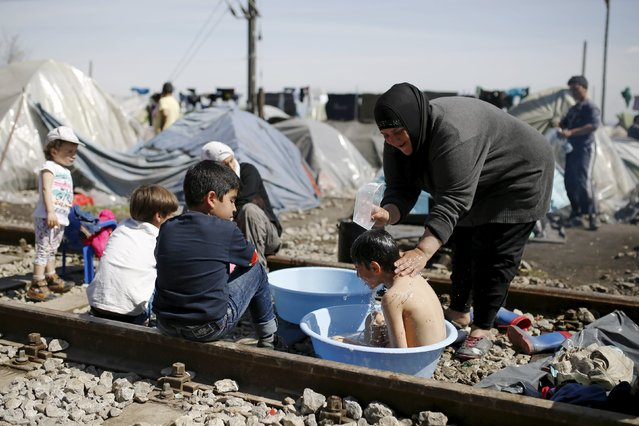 A woman bathes a child at railway tracks at a makeshift camp for migrants and refugees at the Greek-Macedonian border near the village of Idomeni, Greece, March 30, 2016. (Photo by Marko Djurica/Reuters)
