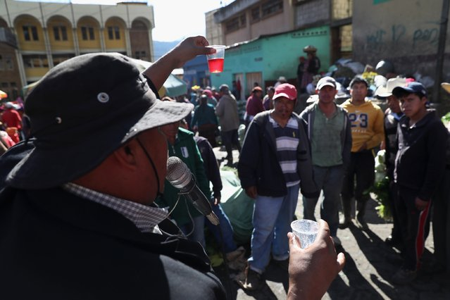 Herbal remedy salesman Wilmer Ruiz shows off his formula to people at a vegetable market on February 11, 2017 in Almolonga, Guatemala. Ruiz said he once tried to cross into the United States but was caught and deported and never tried again. He says his herbal remedy cures a wide range of ailments, including stomach pains, diabetes and hair loss. (Photo by John Moore/Getty Images)