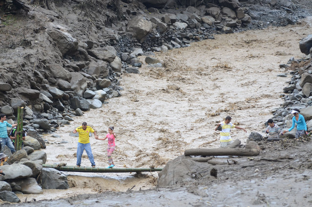 Residents cross an overflowing ravine in Salgar, in Colombia's northwestern state of Antioquia, Tuesday, May 19, 2015, where a deadly flood and mudslide swept through a day earlier. (Photo by Luis Benavides/AP Photo)