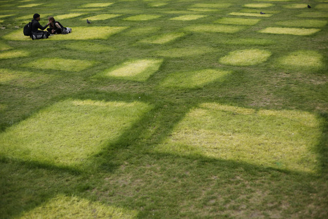 People sit eating next to tent marks outlined on grass from where Extinction Rebellion climate protesters had set up a camp in Marble Arch, London, Friday, April 26, 2019. Extinction Rebellion ended its remaining blockades in London on Thursday evening with a closing ceremony, after disrupting the British capital for 10 days. The non-violent protest group is seeking negotiations with the government on its demand to make slowing climate change a top priority. (Photo by Matt Dunham/AP Photo)