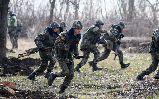 "Ukrainian border guards run during exercises not far from the Alexeevka check point on the border between Ukraine and Russia, some 120 km from the eastern Ukrainian city of Donetsk on March 21, 2014. Ukraine's interim premier Arseniy Yatsenyuk on Friday called for global economic pressure against Russia to halt its drive to forge ""a new world order"". (Photo by Alexander Khudoteply/AFP Photo)"