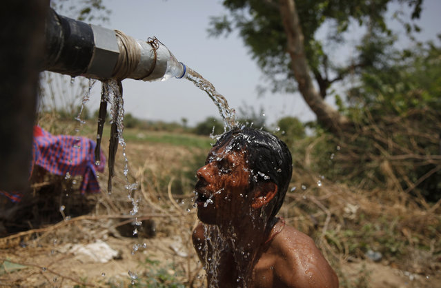 An Indian man takes bath under the tap of a water tanker on a hot day in Ahmadabad, India, Thursday, May 21, 2015. Heat wave conditions prevailed as temperature rises in many parts of India. (Photo by Ajit Solanki/AP Photo)