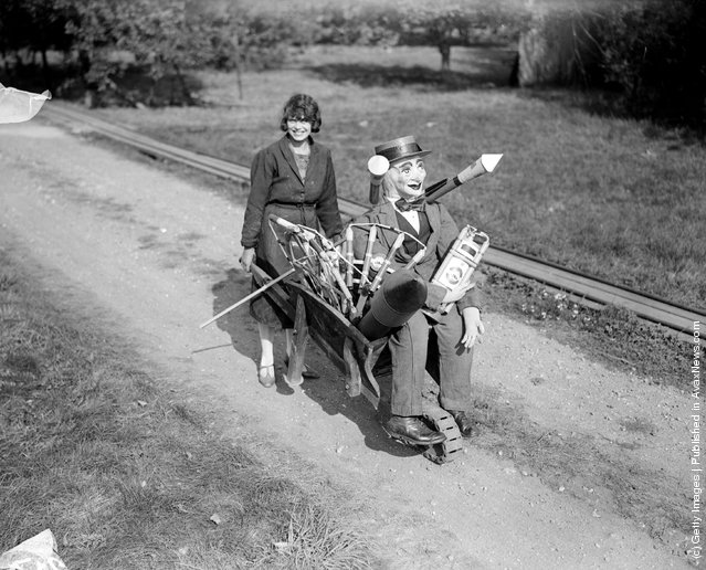 1929: A young woman pushing a guy and a load of fireworks in a wheelbarrow in Surrey