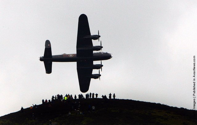 Spectators on a hill look on as a Lancaster bomber flies over Ladybower reservoir in the Derbyshire Peak District to mark the 65th anniversary of the World War II Dambusters mission