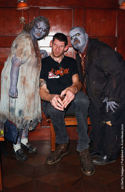 Actor Matthew McGrory poses with zombies