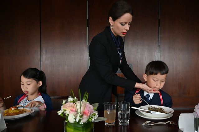 This picture taken on June 1, 2019 shows Miona Milakov teaching children how to sit and eat correctly during an etiquette and manners class in central Shanghai. (Photo by Hector Retamal/AFP Photo)