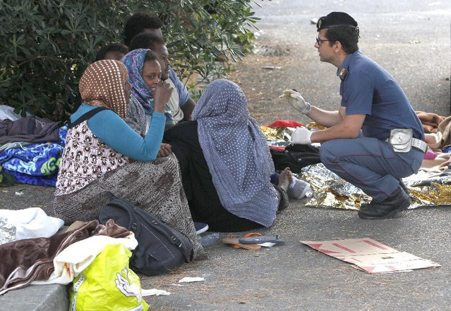 An Italian policeman speaks with migrants during an evacuation attempt at the Franco-Italian border near Menton, southeastern France, Tuesday, June 16, 2015. Some 150 migrants, principally from Eritrea and Sudan, have been trying since last Friday to cross the border from Italy but have been blocked by French and Italian police. (AP Photo/Lionel Cironneau)