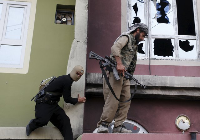 Kurdish gunmen climb the house of a Shi'ite militiaman during clashes in Tuz Khurmato, Iraq, April 24, 2016. (Photo by Goran Tomasevic/Reuters)