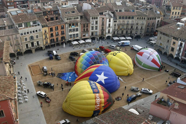 A hot air balloon (2nd L) in the colours of the Estelada (the Catalan seperatist flag) is pictured among other balloons as they are inflated, during the XXXI International Mercat del Ram Balloon Trophy 2014,  at the main square in Vic April 11, 2014. Catalonia's regional parliament unanimously adopted a declaration of self-determination saying the people had the right to vote on breaking away from the rest of Spain. (Photo by Gustau Nacarino/Reuters)