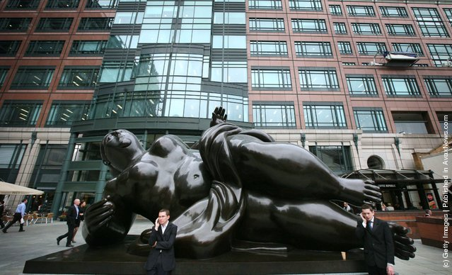 City workers stand by a sculpture of a reclining Venus figure by Fernando Botero in Exchange Square