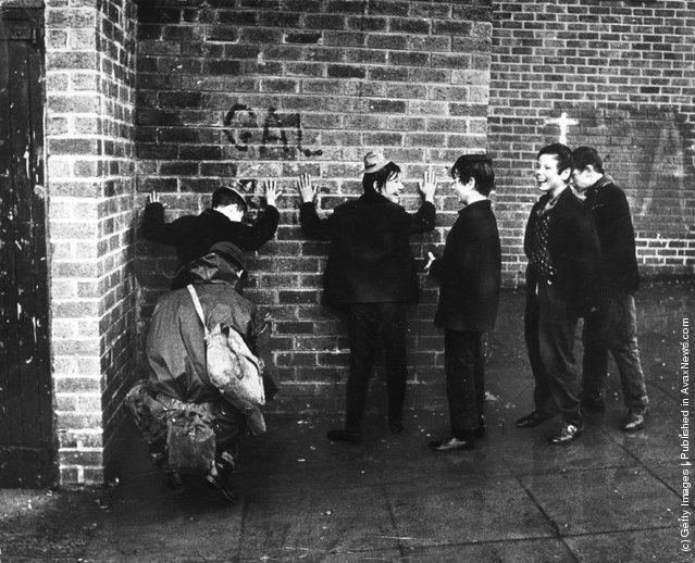 1971:  Schoolboys giggling while a soldier searches them in a street in the Ardoyne area of Belfast