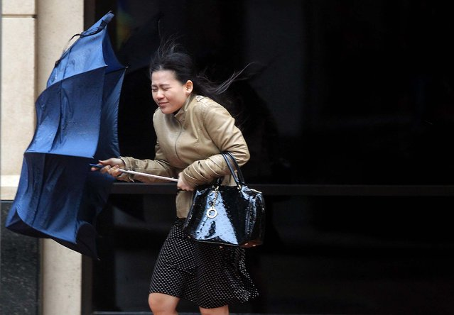 A woman is caught in the wind and rain as a cold front moves into Houston, on April 14, 2014. The cold front has brought snow to the Texas Panhandle, hail to the central part of the state and forecasts for freezing conditions accompanied by strong winds. (Photo by Mayra Beltran/Houston Chronicle)