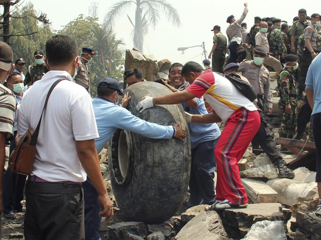Military personnel remove an aircraft wheel at the site where an air force cargo plane crashed in Medan, North Sumatra, Indonesia, Tuesday, June 30, 2015. (Photo by Dedy Zulkifli/AP Photo)