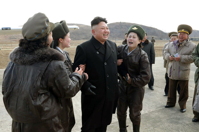 This undated picture released by North Korea's official Korean Central News Agency (KCNA) on March 7, 2014 shows North Korean leader Kim Jong-Un (3rd L) being franked with female pilots as he inspects the Korean People's Army (KPA) Air and Anti-Air Force Unit 2620 honored with the Title of O Jung Hup-led 7th Regiment at an undisclosed location in North Korea. (Photo by AFP Photo/KCNA via KNS)