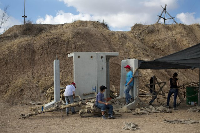 In this Tuesday, June 23, 2015, photo, Israeli youth build a bonfire next to a bomb shelter, during preparation to celebrate their Bar Mitzvah, in Kibbutz Beeri, southern Israel near the border with the Gaza Strip. (Photo by Oded Balilty/AP Photo)