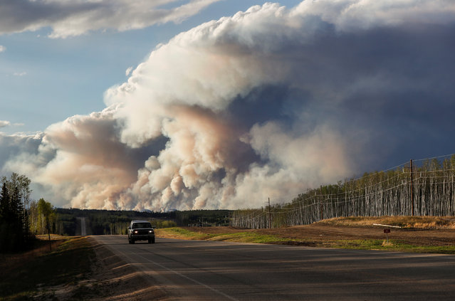 Smoke billows from the Fort McMurray wildfires as a truck drives down the highway in Kinosis, Alberta, Canada, May 5, 2016. (Photo by Mark Blinch/Reuters)