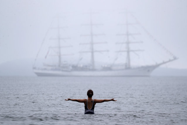 A woman bathing in the Ajax Bay against the background of the sailing ship Nadezhda (Hope) off Russky Island near Vladivostok, Russia on September 6, 2019, during the 5th Eastern Economic Forum (EEF 2019) at the Far Eastern Federal University (FEFU). (Photo by Vladimir Smirnov/TASS Host Photo Agency)