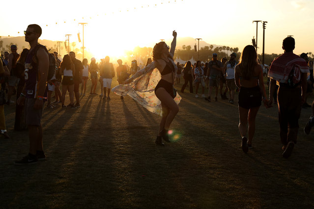 A woman dances at sunset during the Coachella Valley Music and Arts Festival on April 16, 2017 in Indio, California. (Photo by Carlo Allegri/Reuters)