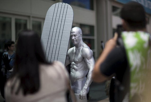 A cosplay enthusiast dressed like the character Silver Surfer poses for photos during the 2015 Comic-Con International Convention in San Diego, California July 10, 2015. (Photo by Mario Anzuoni/Reuters)