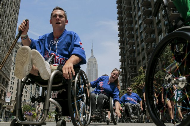 Dan Santos (L), 22, suffering from Femoral Hypoplasia, and Sara Tabor, (C), 33, and Lary Minei, 41, both paraplegic take part in the disability pride parade in New York, July 12, 2015. (Photo by Eduardo Munoz/Reuters)