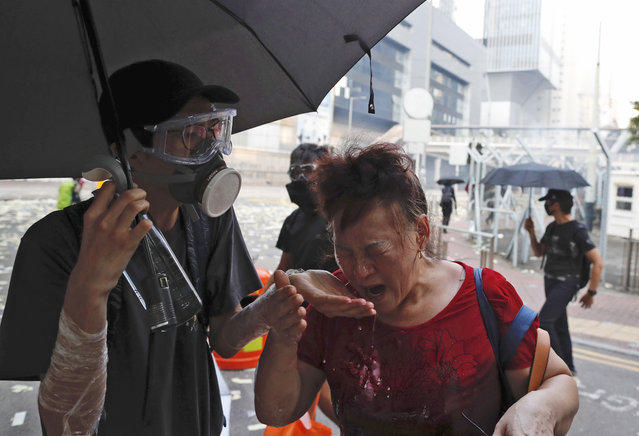 A black-clad protestor splashes water on the face of a woman after police fired tear gas shells in Hong Kong, Tuesday, October 1, 2019. A Hong Kong police official says a pro-democracy protester was shot when an officer opened fire with his revolver during clashes Tuesday. A video of the incident, shot by the City University Student Union and shared on social media, shows a dozen black-clad protesters hurling objects at a group of riot police pursuing them. One officer, who was surrounded, drew his revolver and pointed it at the group. He fired and one protester collapsed on the street while others fled. (Photo by Gemunu Amarasinghe/AP Photo)