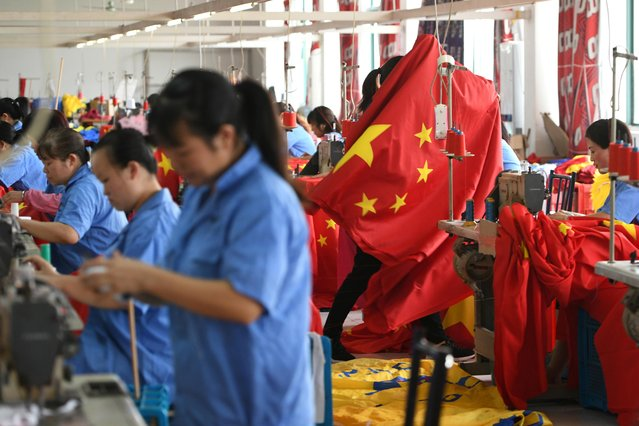 Workers make Chinese flags at a factory ahead of the 70th founding anniversary of People's Republic of China, in Jiaxing, Zhejiang province, September 25, 2019. (Photo by Reuters/China Stringer Network)