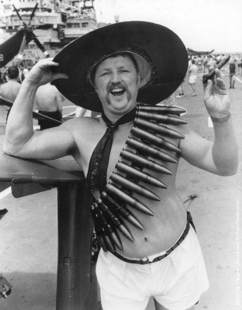 1982: Kenneth 'Rocky' Hudson, a Petty Officer from Gosport aboard HMS Hermes, the flagship of the Royal Navy, heading for the Falkland Islands. The troops are waging a Mexican moustache growing contest and Kenneth is wearing 30mm cannon shells slung around his body and sporting a fat cigar