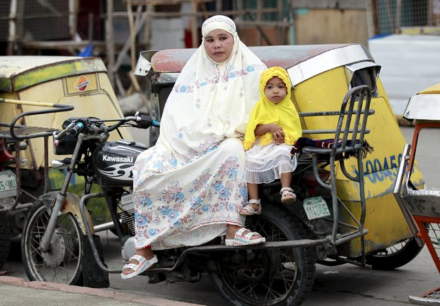 A mother with her daughter sits on a tricycle cab before the start of their morning prayer at a park in a slum area in Tondo, metro Manila July 17, 2015. (Photo by Romeo Ranoco/Reuters)