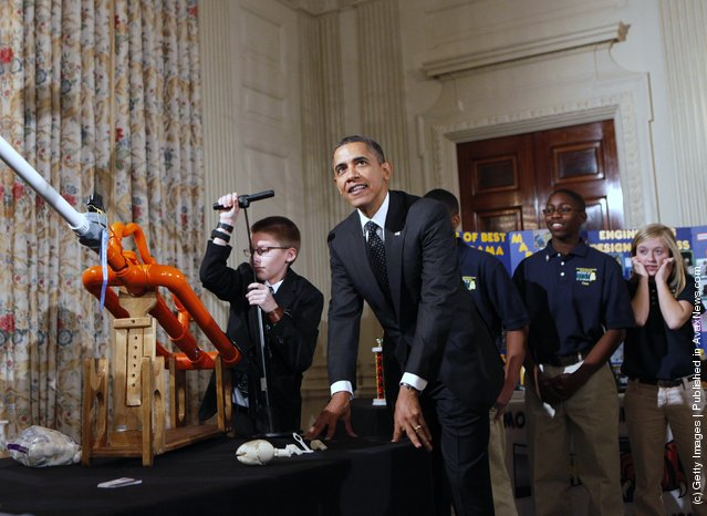 President Barack Obama watches as Joey Hudy (L), 14, from Phoenix, Arizona pumps the Extreme Marshmallow Cannon he invented, while touring student science fair projects on exhibit in the State Dining Room at the White House