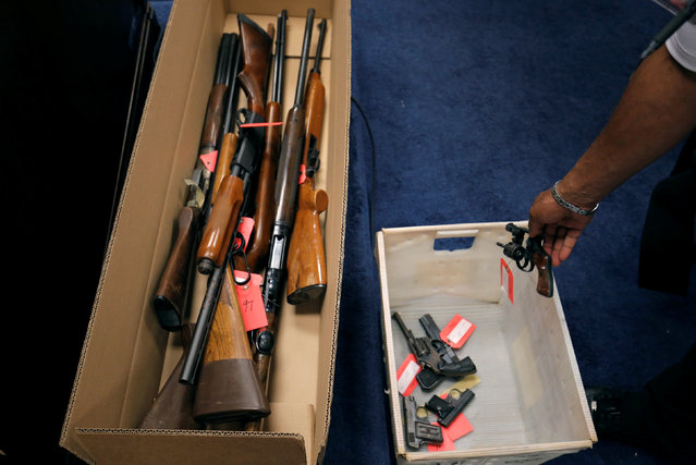 "A Chicago Police officers drops a gun into a box with other firearms  turned in from the public as part of the ""Gun Turn-in"" event where a gift card is given for every firearm turned in at Universal Missionary Baptist Church in Chicago, Illinois, U.S. May 28, 2016. (Photo by Jim Young/Reuters)"