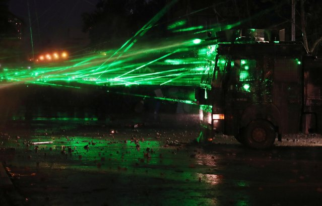 Demonstrators shine lasers on a riot police vehicle during a protest against Chile's government, in Santiago, Chile on November 22, 2019. (Photo by Ivan Alvarado/Reuters)
