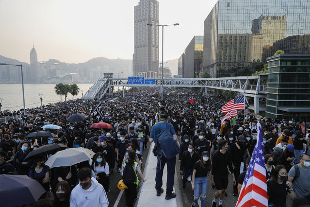 Pro-democracy protesters march on a street during a rally in Hong Kong, Sunday, December 1, 2019. A huge crowd took to the streets of Hong Kong on Sunday, some driven back by tear gas, to demand more democracy and an investigation into the use of force to crack down on the six-month-long anti-government demonstrations. (Photo by Vincent Thian/AP Photo)