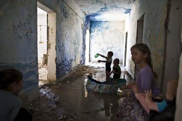 Children play in a plastic pool inside an abandoned building at the evacuated settlement of Sa-Nur in the West Bank July 28, 2015. About 250 right wing protesters defied an Israeli Defense Force (IDF) decree and entered the former West Bank settlement of Sa-Nur Israel evacuated during the 2005 disengagement. (Photo by Nir Elias/Reuters)
