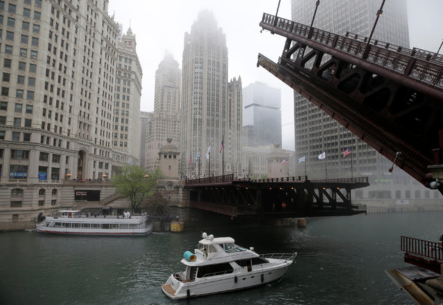A boat passes under a raised bridge across from the Chicago Tribune building (C) in Chicago, Illinois, United States, May 11, 2016. (Photo by Jim Young/Reuters)