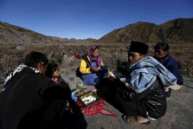 Hindu villagers eat their breakfast after collecting holy water from a stream for prayers ahead of the annual Kasada festival at Mount Bromo in Indonesia's East Java province, July 31, 2015. (Photo by Reuters/Beawiharta)