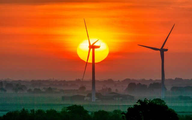 Sunrise over a wind farm at Tick Fen, Cambridgeshire, England yesterday, May 20, 2019. It will be sunny and dry across large parts of the UK today. (Photo by Andrew Sharpe/Geoff Robinson Photography)