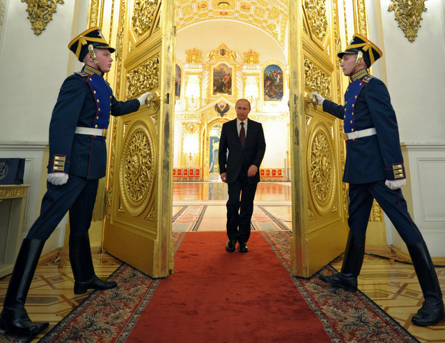 Russian President Vladimir Putin enters a hall to attend the presentation ceremony of the top military brass in the Kremlin in Moscow, Russia, Friday, March 28, 2014. Russia's president says Ukraine could regain some arms and equipment of military units in Crimea that did not switch their loyalty to Russia. (Photo by Alexei Druzhinin/AP Photo/RIA-Novosti/Presidential Press Service)