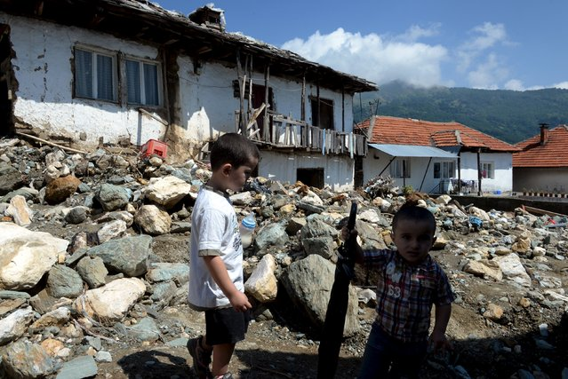 Boys stand on a street in the flooded village of Shipkovitsa, near the town of Tetovo, Macedonia, August 4, 2015. (Photo by Reuters/Stringer)