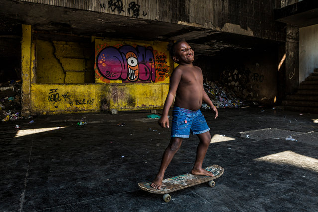 A child rides her skateboard in the Brazilian Institute of Geography and Statistics (IBGE) building in Mangueira. (Photo by Tariq Zaidi/The Guardian)