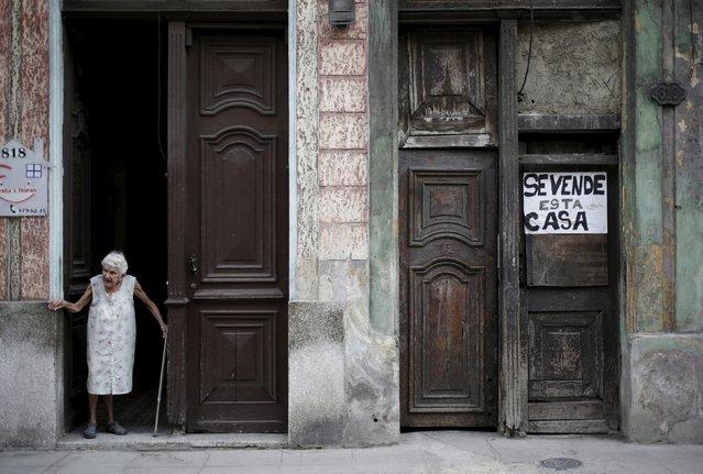 An old woman stands near a house for sale in Havana April 10, 2015. (Photo by Enrique De La Osa/Reuters)