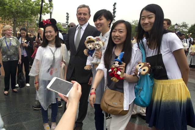 Disney CEO Bob Iger poses for photos with visitors on the opening day of the Disney Resort in Shanghai, China, Thursday, June 16, 2016. (Photo by Ng Han Guan/AP Photo)