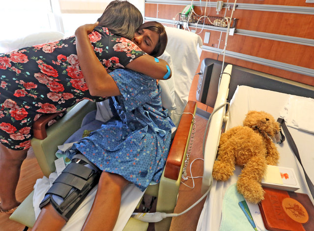 Tiara Parker, left, and her friend Patience Carter, both victims in the Pulse nightclub shooting, embrace as they share a moment at in Carter's Florida Hospital Room before they meet President Obama, Thursday, June 16, 2016, in Orlando Fla. Carter and Parker layed on the floor with gunshot wounds while their captor, gunman Omar Mateen, terrorized her and several others in a bathroom at the nightclub. (Photo by Red Huber/Orlando Sentinel via AP Photo)