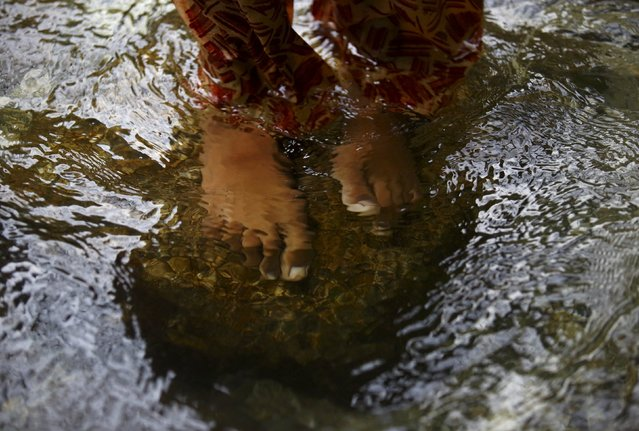 """The bare feet of a Hindu devotee are pictured underwater as she stands on Bagmati River while offering prayers during the """"Bol Bom"""" pilgrimage in Kathmandu August 10, 2015. (Photo by Navesh Chitrakar/Reuters)"""