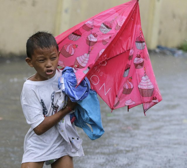 A boy evacuates to safer grounds at the onslaught of Typhoon Rammasun (locally known as Glenda) which battered the city Wednesday, July 16, 2014, in Manila, Philippines. (Photo by Bullit Marquez/AP Photo)