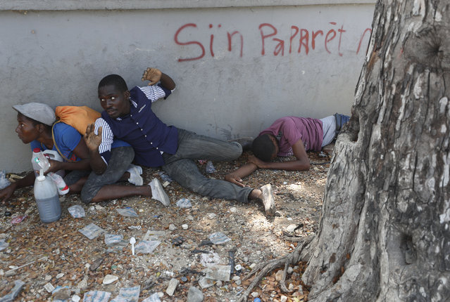 Demonstrators who were carrying the coffins with the remains of two victims of the ongoing violence take shelter after clashes erupted between demonstrators and the Presidential Guard, near the Presidential Palace in Port-au-Prince, Haiti, Wednesday, October 16, 2019. At last two people were injured in the clashes the while thousands across Haiti attended funerals for protesters who have died in ongoing demonstrations aimed at ousting President Jovenel Moise. (Photo by Rebecca Blackwell/AP Photo)
