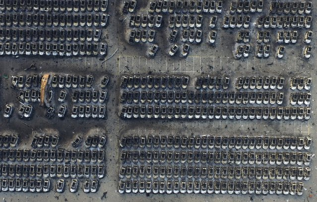 An aerial picture shows damaged vehicles near the site of Wednesday night's explosions at Binhai new district in Tianjin, China, August 15, 2015. (Photo by Reuters/Stringer)