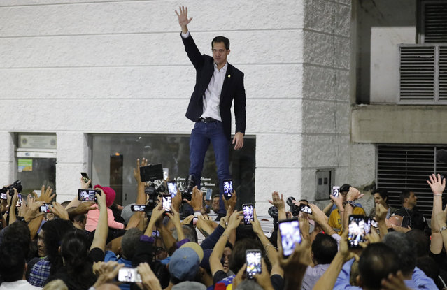 Opposition leader Juan Guaido waves to supporters during a rally at Bolivar Plaza in Chacao, Venezuela, Tuesday, February 11, 2020. Guaido returned home from a tour of nations that back his effort to oust socialist leader Nicolas Maduro. (Photo by Ariana Cubillos/AP Photo)