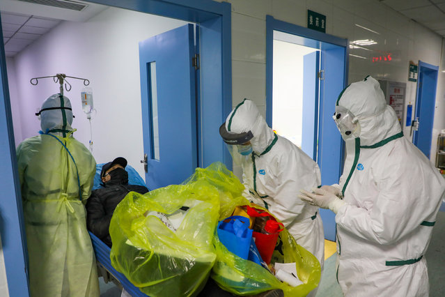 Medical workers in protective suits move a novel coronavirus patient at an isolated ward of a designated hospital in Wuhan, Hubei province, China on February 6, 2020. (Photo by Reuters/China Daily)