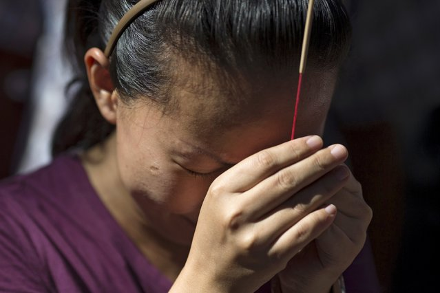 A family member of Malaysians victims pays her respect during a Buddhist ceremony at the Erawan shrine, the site of Monday's deadly blast, in central Bangkok, Thailand, August 19, 2015. (Photo by Athit Perawongmetha/Reuters)